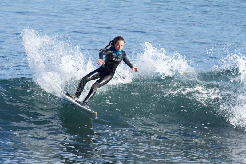 Jeune fille surfant une vague en Californie images stock