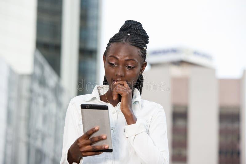 Jeune fille surprise tenant le téléphone portable en dehors de la salle image stock