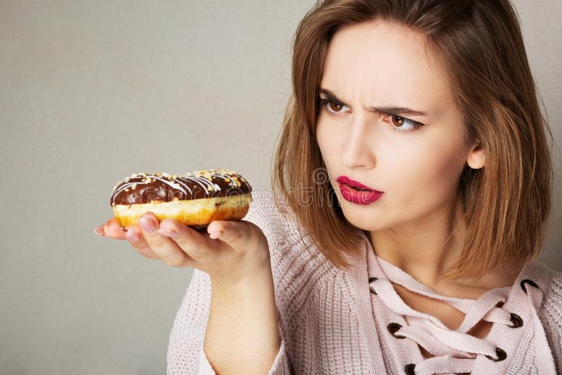 Jeune fille suspecte avec les lèvres roses tenant le beignet de chocolat au-dessus d'un fond gris L'espace pour le texte image stock