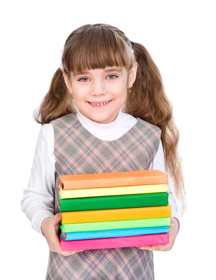 Jeune fille tenant des livres de pile D'isolement sur le fond blanc image stock