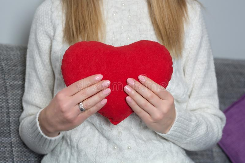Jeune fille tenant le grand oreiller rouge de coeur à disposition sur son coffre à la maison photographie stock