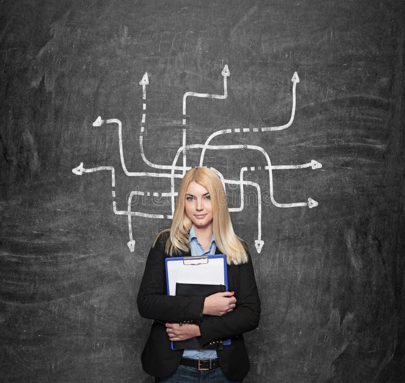 Jeune fille tenant les carnets, labirinth au fond image stock