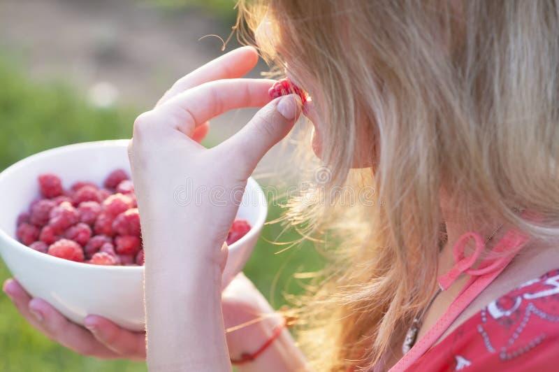 Jeune fille tenant un plat des framboises, se reposant sur l'herbe verte, ?t?, dessert photo stock