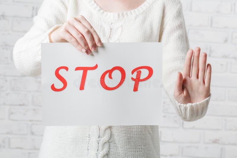 Jeune fille tenant un signe blanc avec l'ARRÊT rouge d'inscription sur W images libres de droits