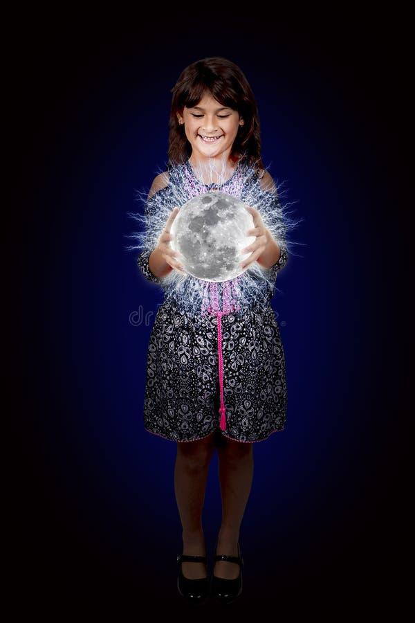 Jeune fille tenant une lune lumineuse de plasma photographie stock libre de droits