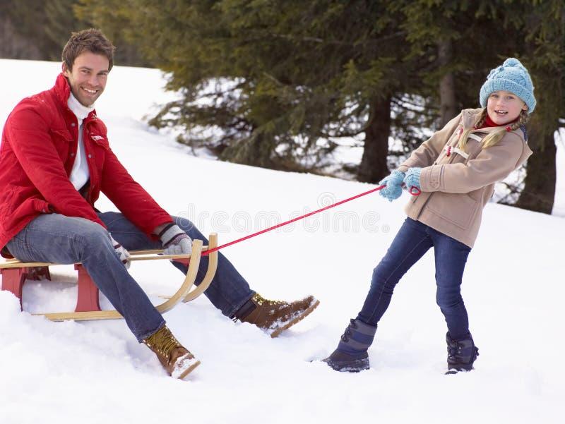 Jeune fille tirant le père par la neige sur le traîneau photos libres de droits
