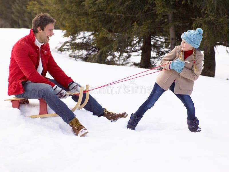 Jeune fille tirant le père par la neige sur le traîneau photographie stock