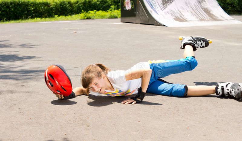 Jeune fille tombant tandis que patinage de rouleau image libre de droits