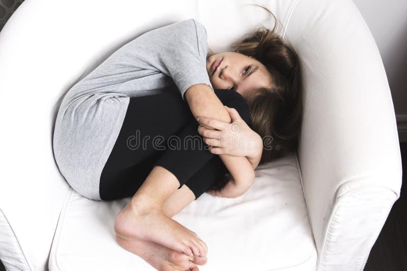 Jeune fille triste étendue sur le sofa images stock