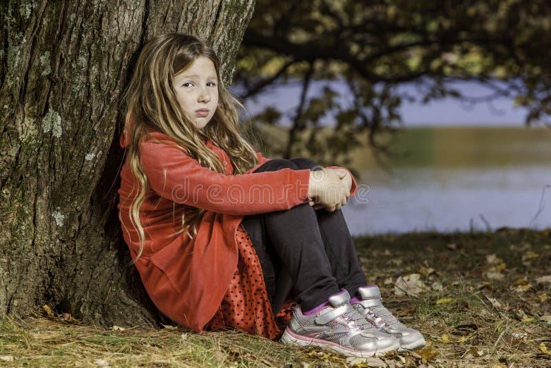 Jeune fille triste par l'arbre photo libre de droits