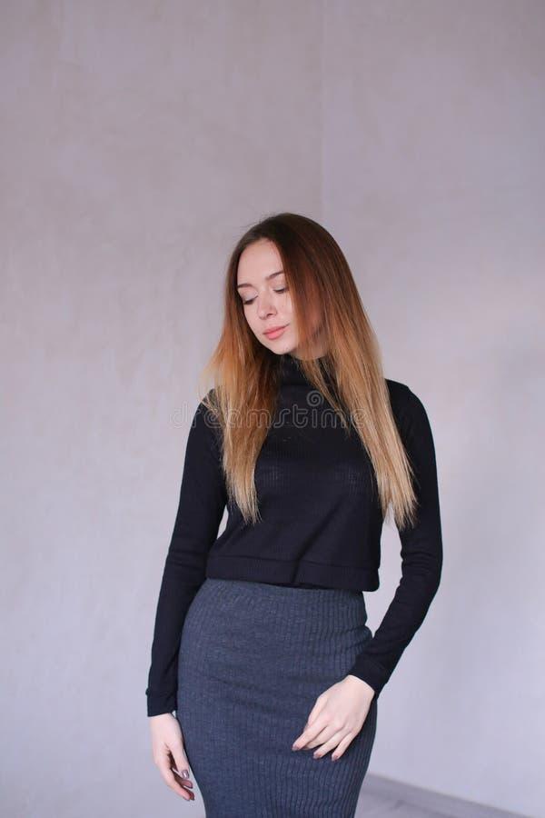 Jeune fille utilisant le chemisier noir et la chemise grise se tenant à l'arrière-plan monophonique images libres de droits