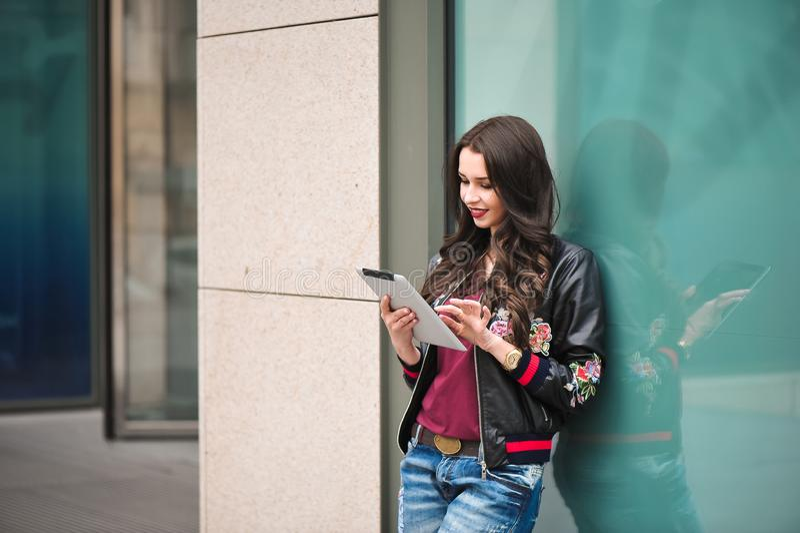 Jeune fille utilisant le comprimé dans la rue, style de hippie, portrait extérieur, visage heureux photographie stock libre de droits