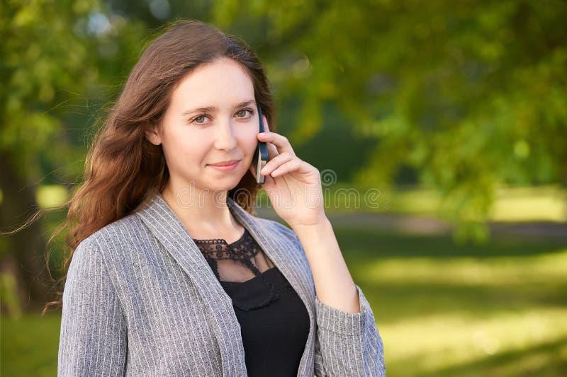Jeune fille utilisant le téléphone portable dehors Femme de la jeunesse parlant comme le conseiller Affaires de causerie images stock