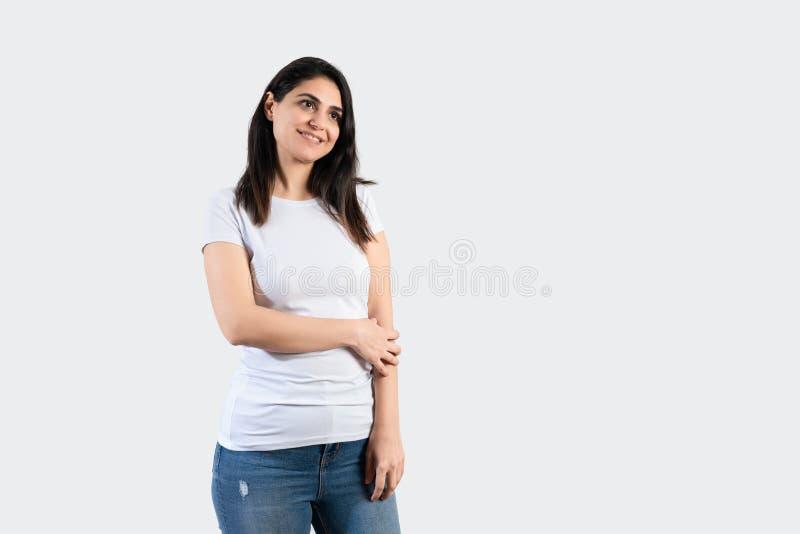 Jeune fille utilisant le T-shirt et les blues-jean blancs vides Fond gris de mur images libres de droits