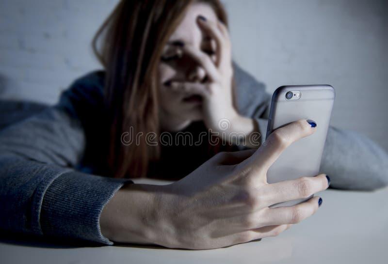 Jeune fille vulnérable triste employant le téléphone portable effrayé et le desperat photographie stock