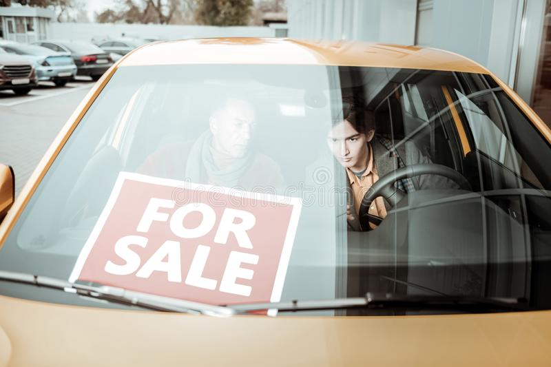Jeune fils et son père de soin s'asseyant dans la voiture orange à vendre photographie stock
