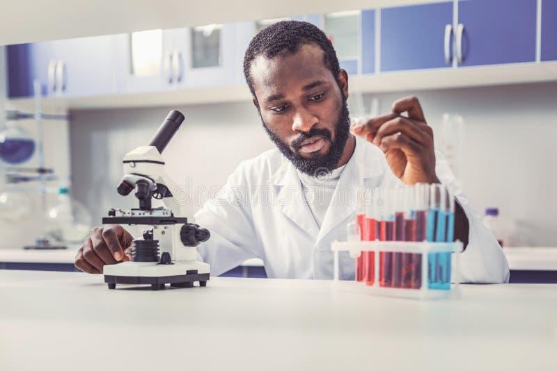 Jeune fonctionnement barbu de chercheur biologiste avec des tubes de verre photographie stock libre de droits