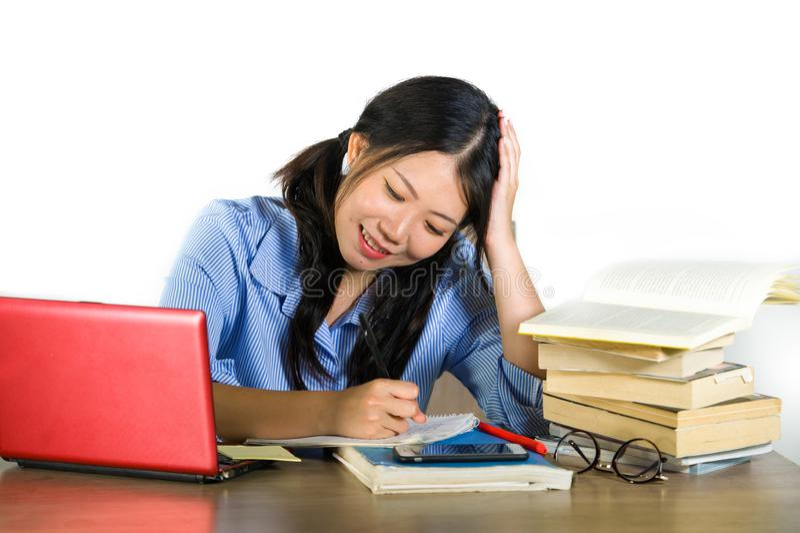 Jeune fonctionnement heureux de sourire de fille chinoise asiatique heureuse et mignonne d'étudiant et étude avec les texbooks et image stock