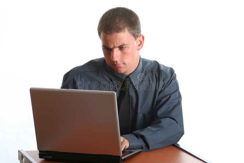 Jeune fonctionnement mâle sur l'ordinateur portatif photo libre de droits