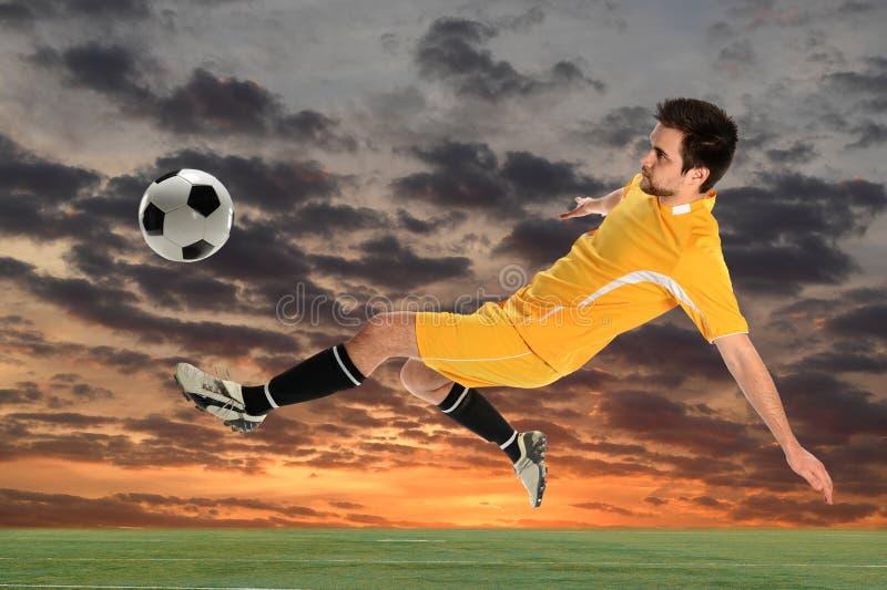 Jeune footballeur donnant un coup de pied la boule photographie stock