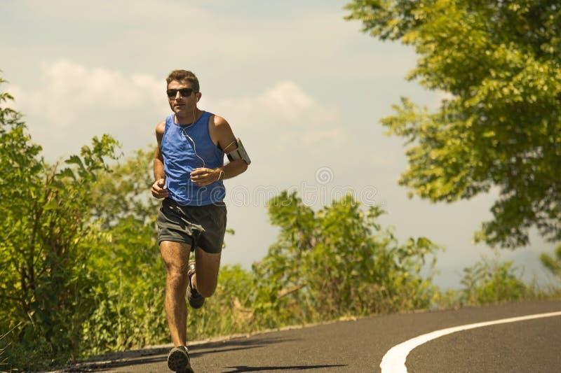 Jeune formation attrayante d'homme de coureur de sport dans la séance d'entraînement courante de route goudronnée par matin ensol photo stock