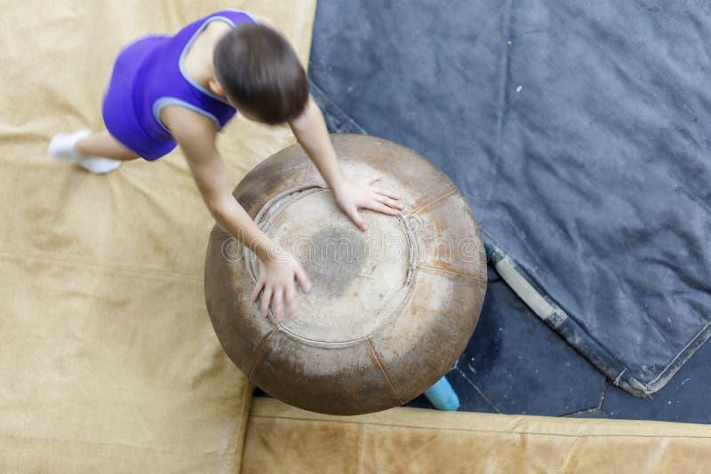 Jeune formation de garçon de gymnastique artistique sur le champignon photographie stock libre de droits