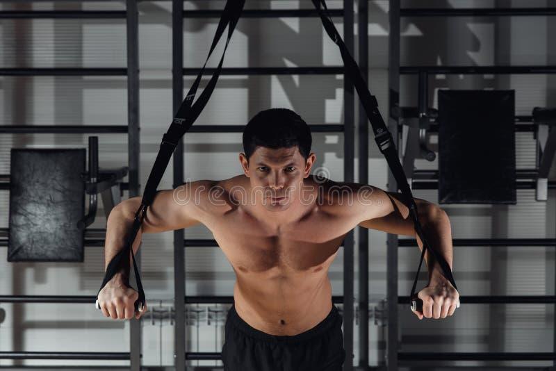 Jeune formation musculeuse belle d'homme avec le trx tout en établissant dans le gymnase image libre de droits