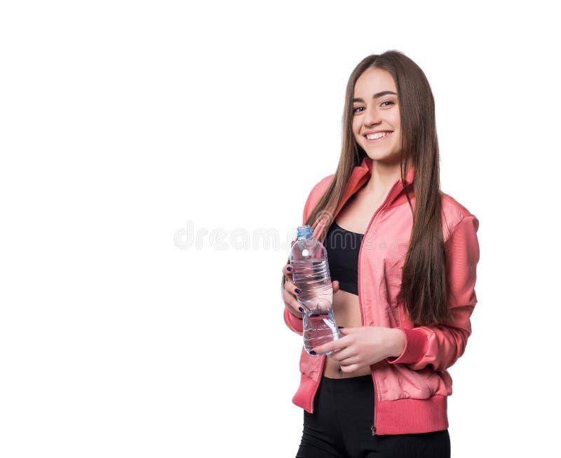 Jeune forme-fille de sourire dans les vêtements de sport avec la bouteille de l'eau pure d'isolement sur le fond blanc Concept sa photographie stock