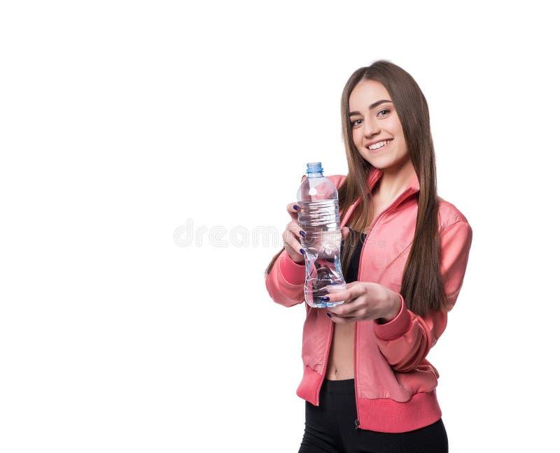 Jeune forme-fille de sourire dans les vêtements de sport avec la bouteille de l'eau pure d'isolement sur le fond blanc Concept sa photographie stock libre de droits