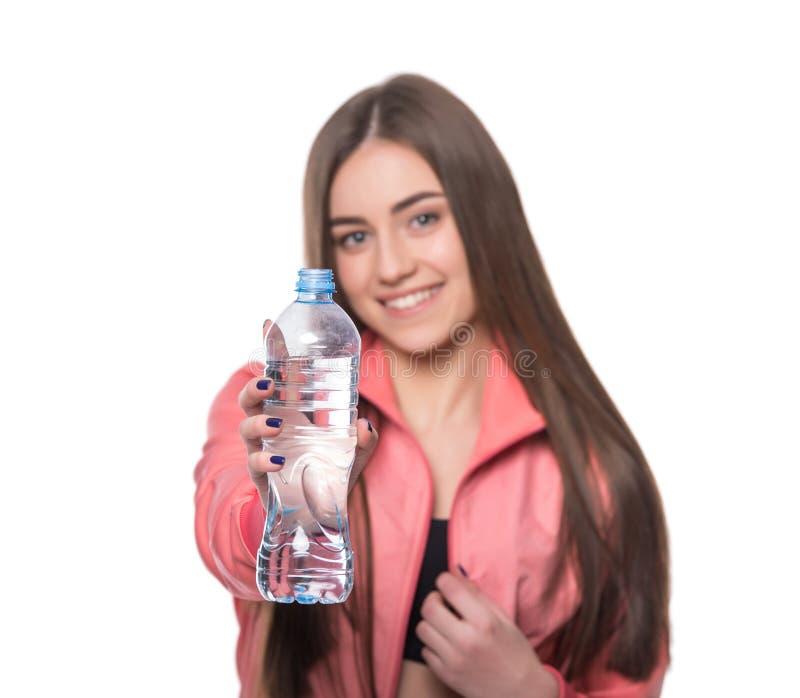 Jeune forme-fille de sourire dans les vêtements de sport avec la bouteille de l'eau pure d'isolement sur le fond blanc Concept sa images libres de droits