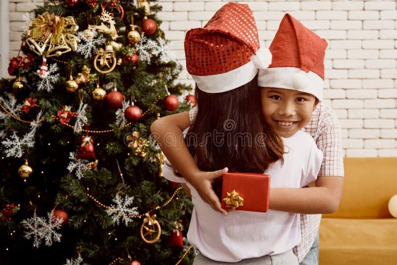 Jeune frère étreignant la soeur tout en tenant le boîte-cadeau derrière photographie stock libre de droits