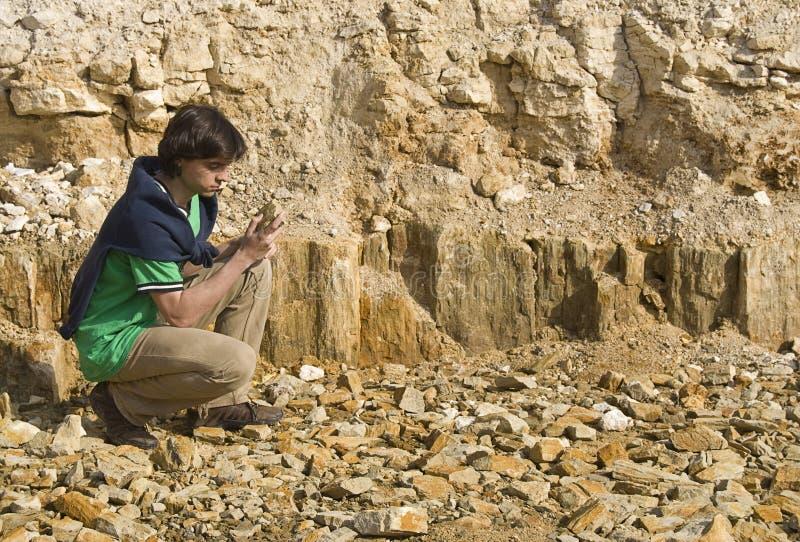 Jeune géologue étudiant le type de roche photo libre de droits