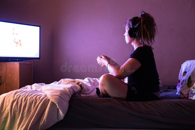 Jeune gamer d'adolescent avec le casque jouant le jeu vidéo à la maison dans la chambre noire utilisant le contrôleur de console  images stock