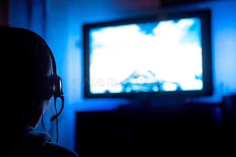 Jeune gamer masculin jouant le jeu vidéo à la maison photographie stock