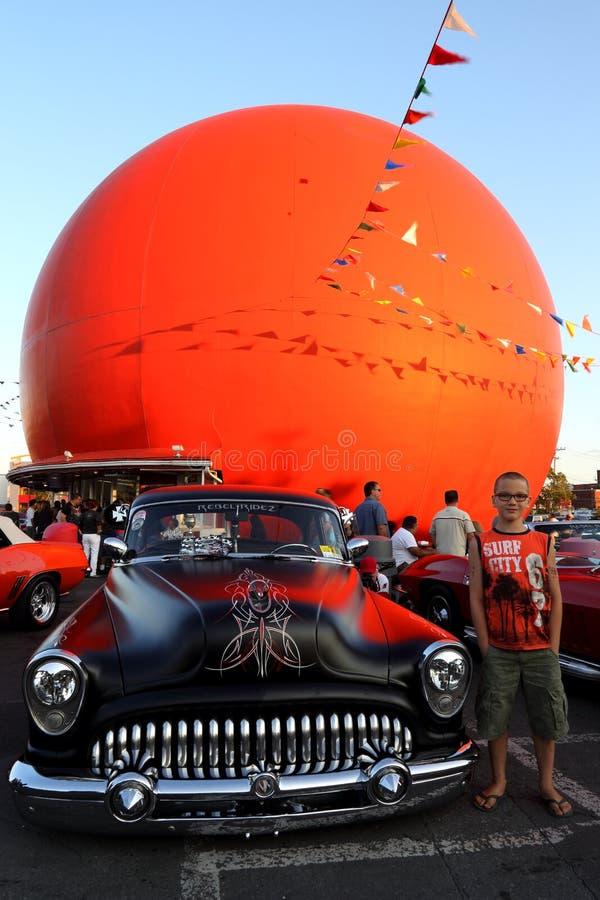 Jeune garçon à côté de voiture noire au salon automobile orange de classique de restaurant's de julep de Gibeau photographie stock