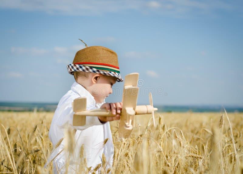 Jeune garçon à la mode jouant dans un domaine avec un avion photo stock