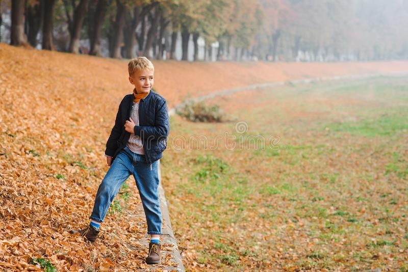 Jeune garçon élégant de sourire dehors en automne Badinez avoir l'amusement dans le parc de ville d'automne parmi les feuilles to photo libre de droits