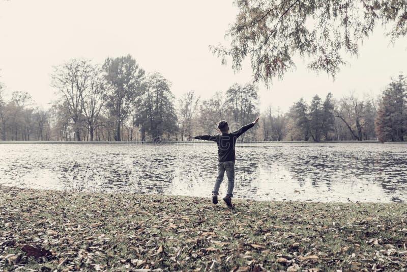 Jeune garçon énergique sautant pour la joie avec les bras tendus image stock