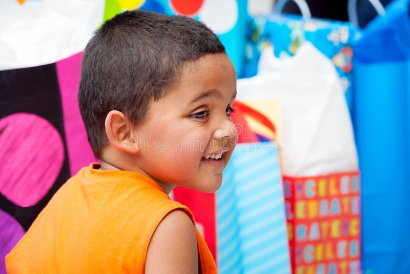 Jeune garçon adorable environ pour ouvrir des cadeaux d'anniversaire image libre de droits