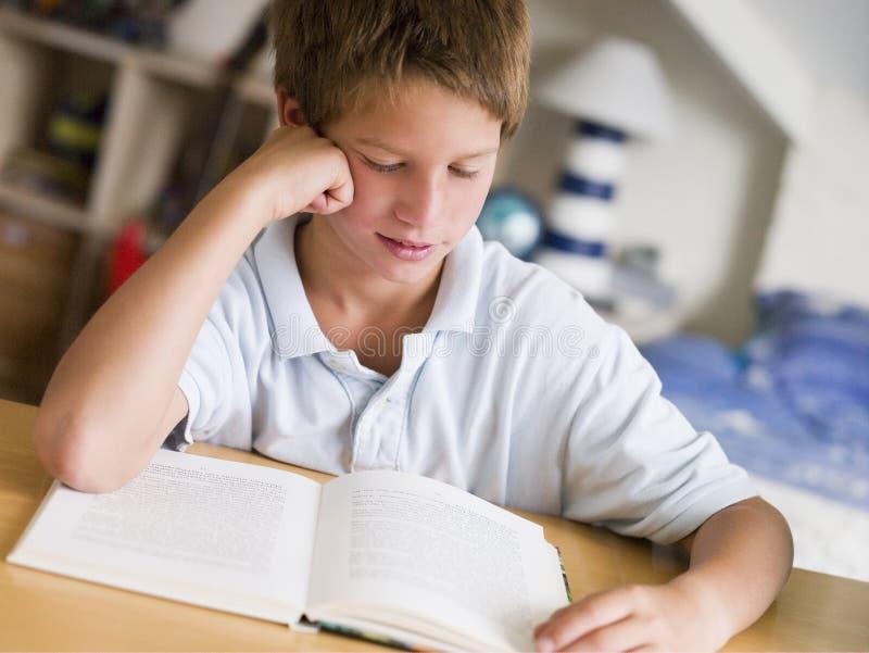 Jeune garçon affichant un livre dans sa chambre images libres de droits