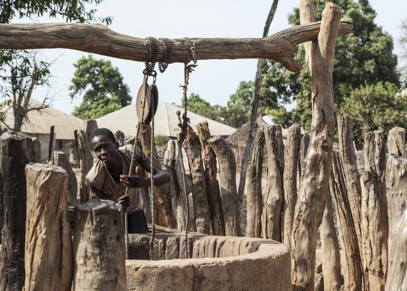 Jeune garçon africain obtenant l'eau d'un manuel bien images libres de droits