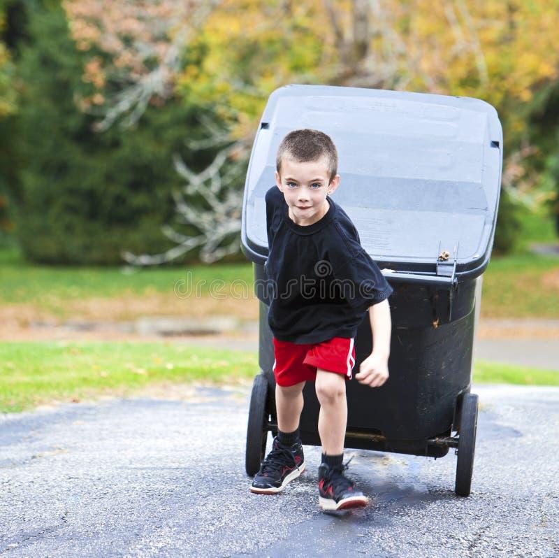 Jeune garçon apportant la poubelle  photographie stock libre de droits