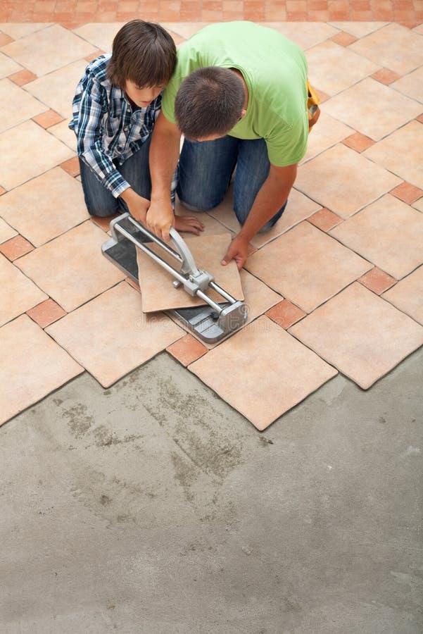 Jeune garçon apprenant comment couper un carrelage en céramique photo libre de droits