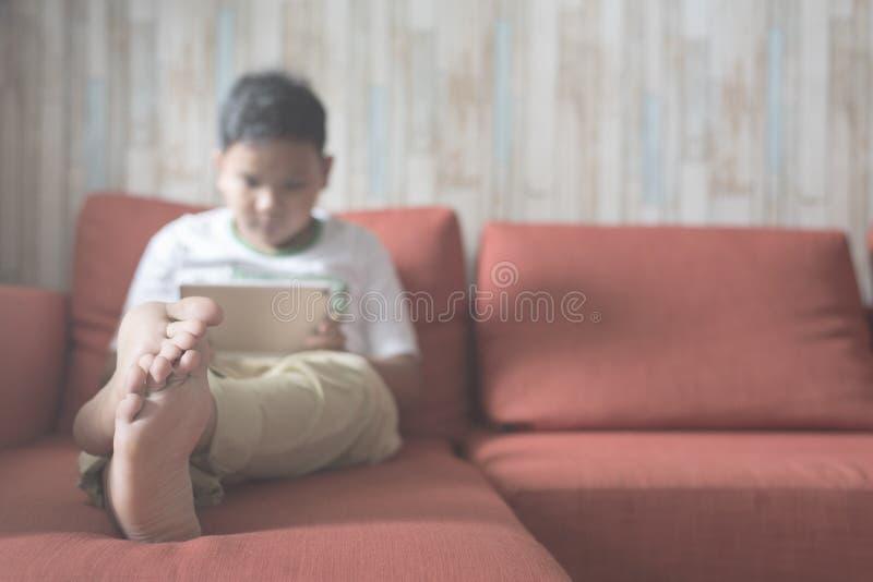 Jeune garçon asiatique à l'aide du comprimé numérique sur un foyer de sofa à la maison sur des pieds image stock