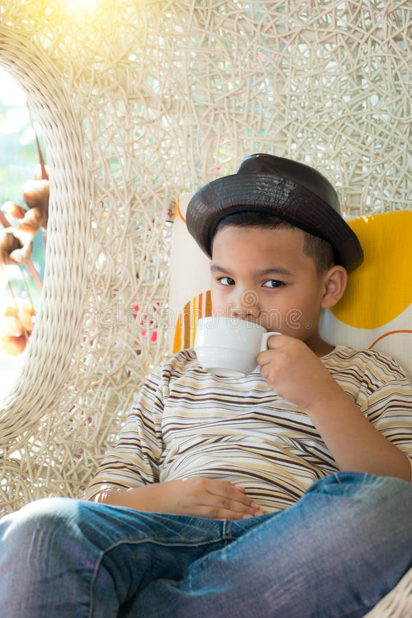 Jeune garçon asiatique beau, buvant d'un lait image stock