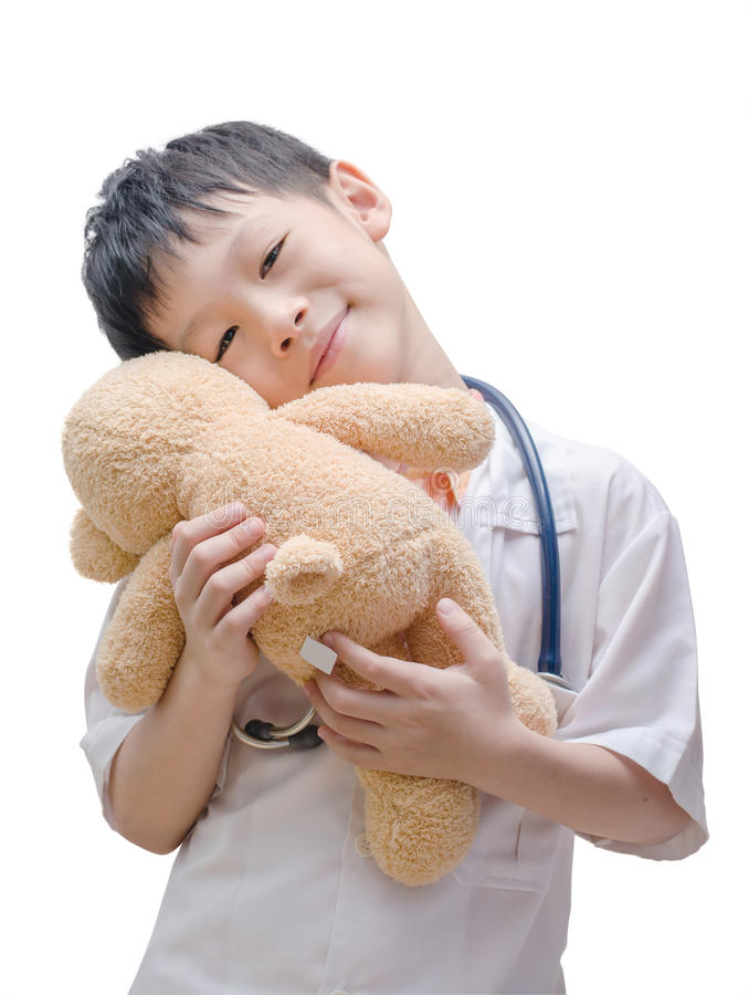 Jeune garçon asiatique de docteur jouant et traitant le jouet d'ours images libres de droits