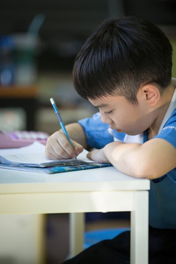 Jeune garçon asiatique faisant son travail photographie stock libre de droits