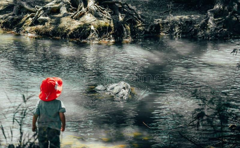 Jeune garçon au bas de la page de la rivière image stock