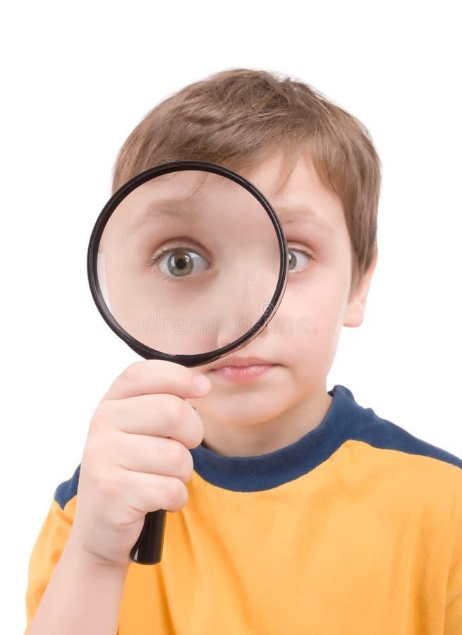 Jeune garçon avec des glas de agrandissement photographie stock libre de droits