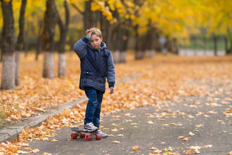 Jeune garçon avec la planche à roulettes et sa main au front photos stock